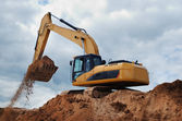 Excavator with earth in the bucket — Stock Photo