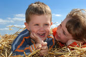 Smiling boy and girl in straw outdoors c — Foto de Stock