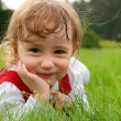 Close-up little girl on the green grass — Stock Photo