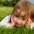 Stock Photo: Close-up little girl on the green grass