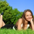 Girl relaxing outdoors lying on the gras — Stock Photo