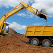 Excavator loading dumper truck - Stock Photo