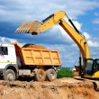 Excavator loading dumper truck — Stock Photo