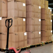 Catron boxes and pallet truck in warehou - 