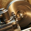 Facing metal blank by cutter on lathe - Stock Photo