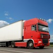 Red lorry with white trailer over blue s — Stock Photo #1053014