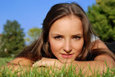 Girl outdoors lying on the grass — Stock Photo