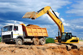 Excavator loading dumper truck — Photo