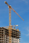 Yellow tower crane building a multistory — Stock Photo