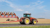 Tractor moving plough on the road — Stock Photo