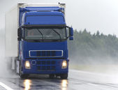 Blue Lorry on wet road — Stock Photo