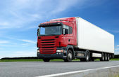 Red lorry with white trailer over blue s — Stok fotoğraf