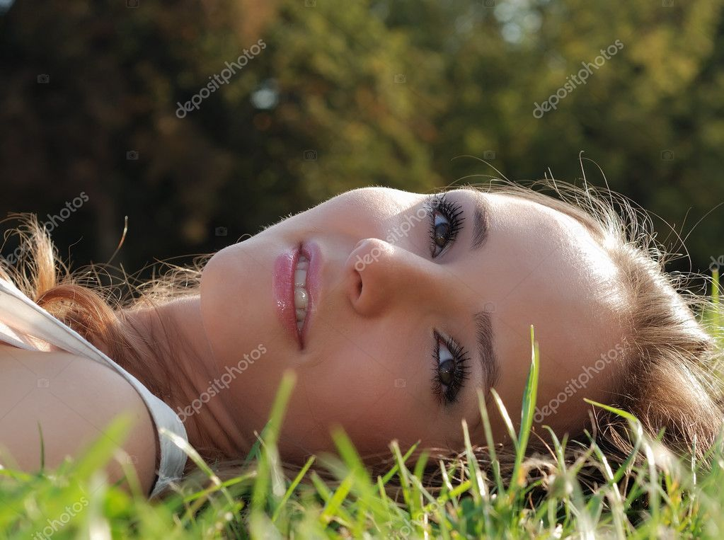 Beautiful young girl relaxing outdoors in summer on grass — Stock Photo #1050860