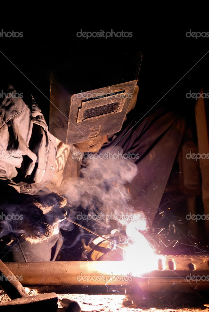 Welder at work with electrode and welding arc — Stock Photo #1051091