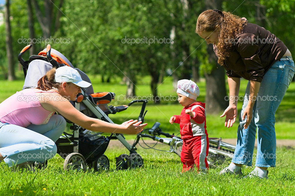 Two women help toddler to do first steps in the park. Green grass and foliage around they. It`s a summer. Baby carriage and bike are here too. — Stock Photo #1022225
