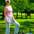 Royalty-Free Stock Photo: Woman cyclist stays near lying bike