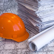 Orange helmet and heap of project drawin — Stock Photo