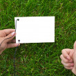 Hands and paper on grass — Stock Photo