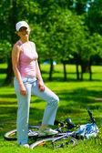Woman cyclist stays near lying bike — Stock Photo