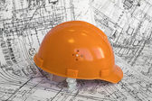 Orange helmet and project drawings — Stock Photo