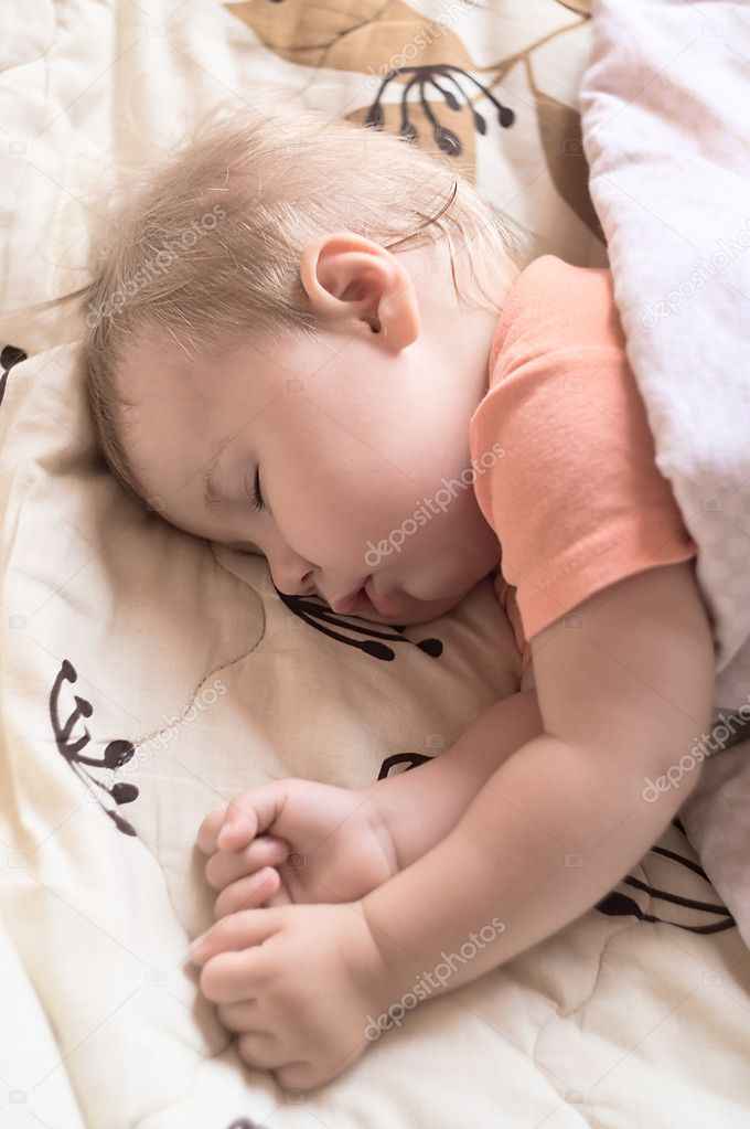 Closeup of sleeping baby lying on white blanket in a comfortable position. Soft focus around  Stock Photo #1030723