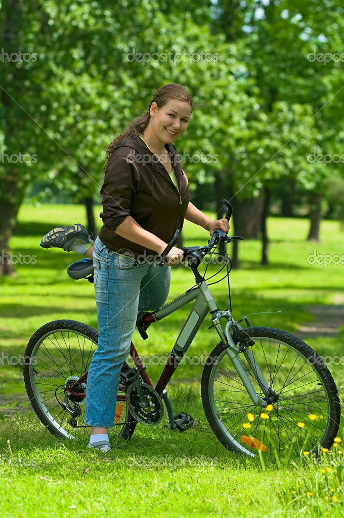 Young woman biker on the bicycle stand in the park. She gets on bike and will going to ride. It`s a hot summer. — Stock Photo #1033197