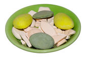 Green plate with color pebbles — Stock Photo