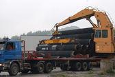 Crane loading pipes in the semi-truck — Stock Photo