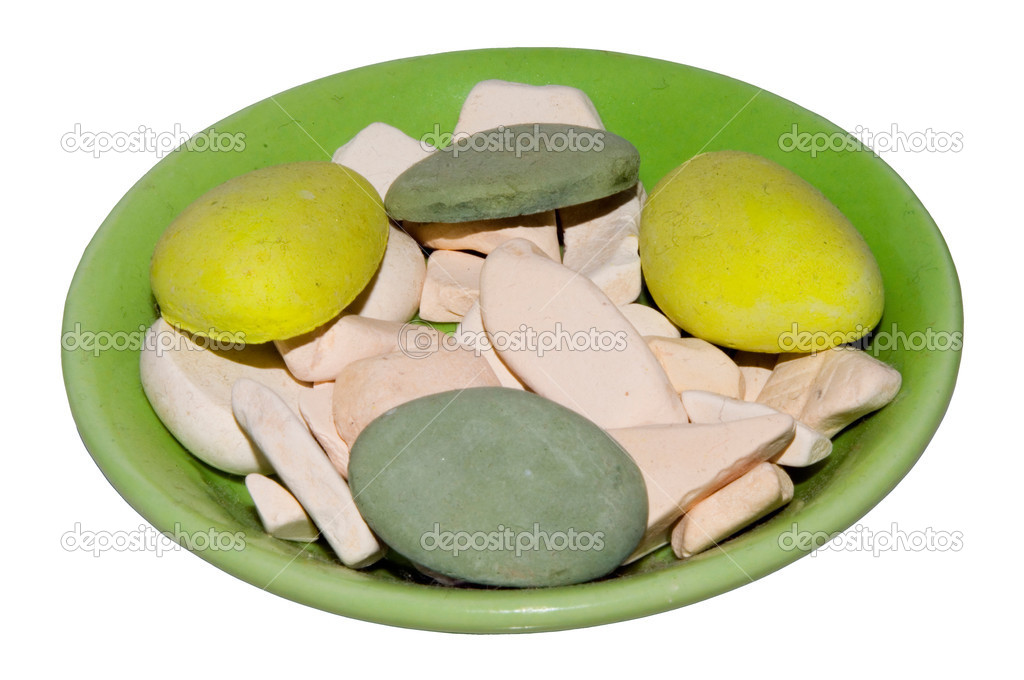 Green plate with round color pebbles. Theirs colors are yellow, grey and white.    #1043597