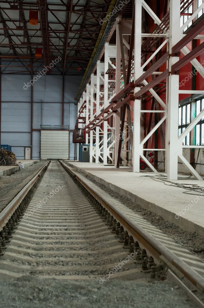 Railroad going into the distance in hangar near from hardware. Metal columns and ceiling. — Stock Photo #1044290