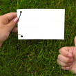 Hands and paper on grass — Stock Photo #1056367