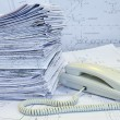 White phone and heap of project drawings — Stock Photo