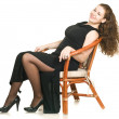 Young woman in black dress on chair — Foto Stock