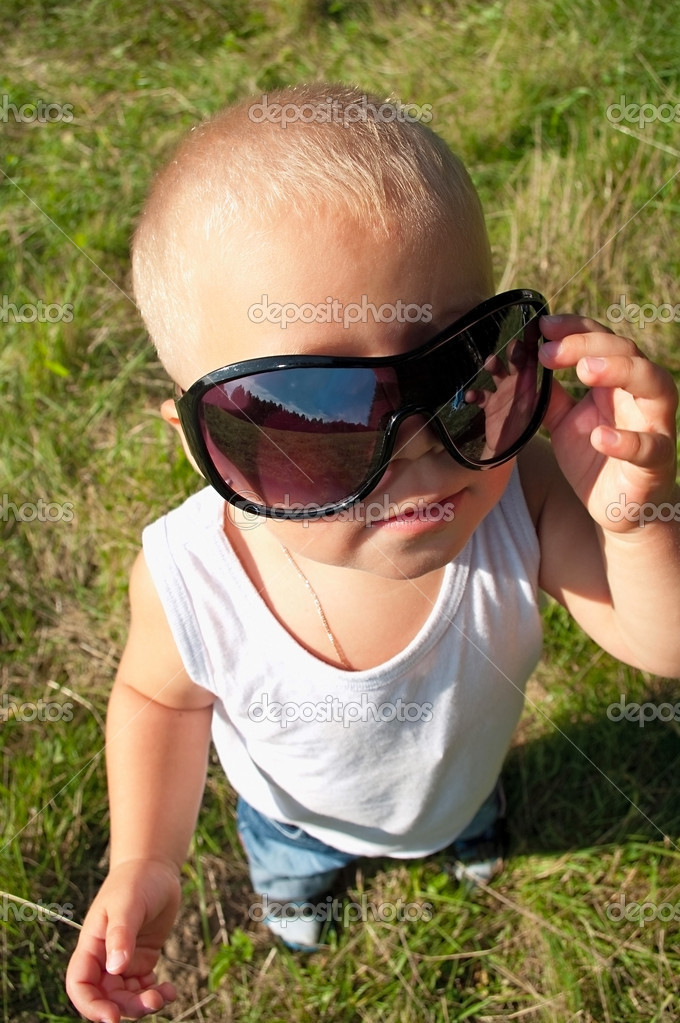 One little child in sunglasses standing on grass. Top view shot. Fish-eye — Stock Photo #2258982