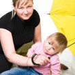 Stock Photo: Mother and little child under umbrella