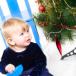 Little girl playing near Christmas tree - Stock Photo