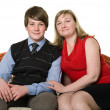Young mother and teenage son on sofa — Stock Photo