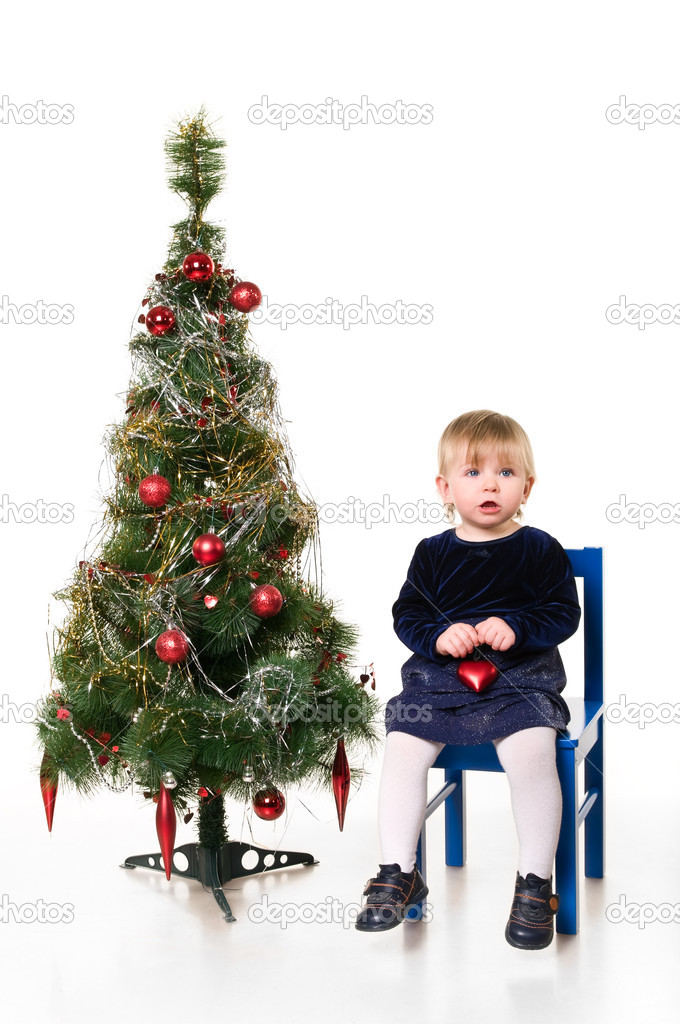 One little child a girl is sitting near the Christmas tree on chair. Isolated on white background.  — Stock Photo #2431429