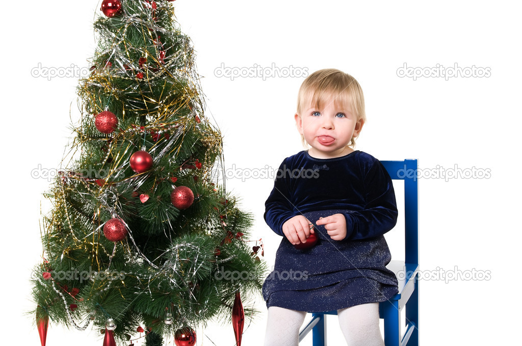 One little child a girl is sitting near the Christmas tree on chair. Isolated on white background.  — Stock Photo #2431443