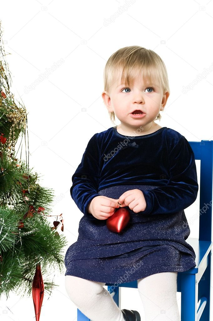 One little child a girl is sitting near the Christmas tree on chair. Isolated on white background.  — Stock Photo #2431912