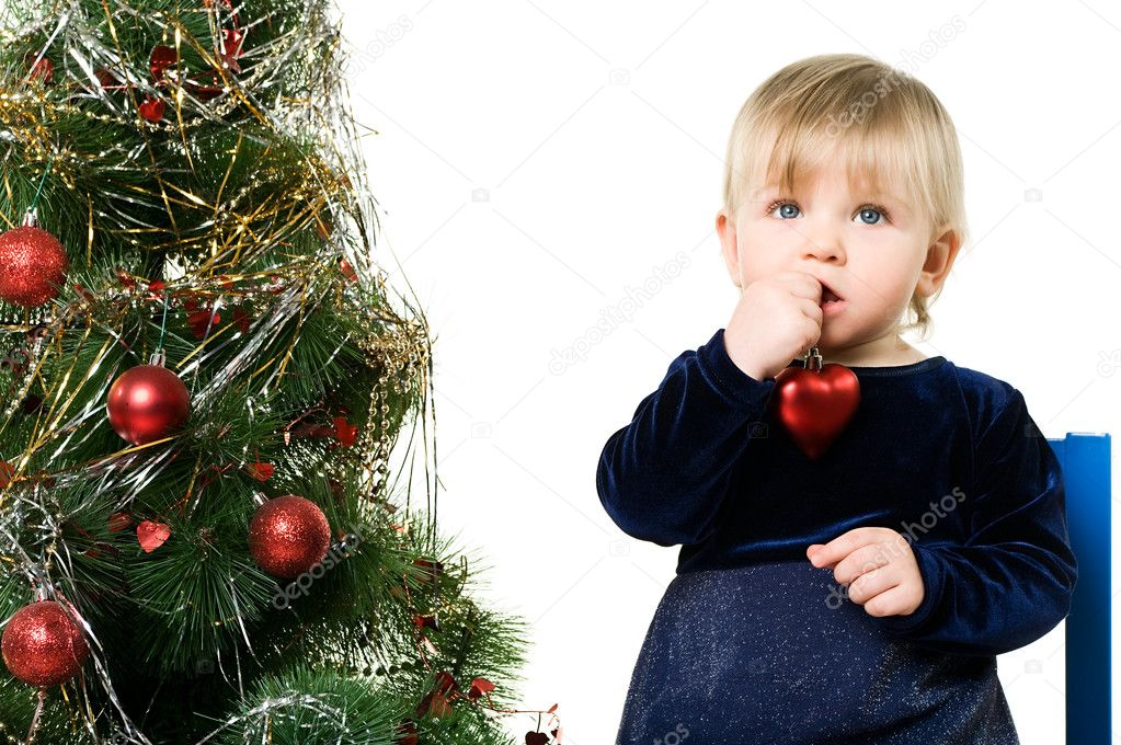 One little child a girl is sitting near the Christmas tree on chair. Isolated on white background.  — Stock Photo #2431923