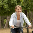 Young female riding smiling bike - Stock Photo