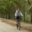 Stock Photo: Young female riding smiling bike