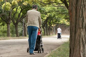 Fathers walking with a carriage — Stock Photo