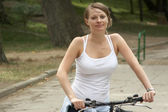 Young female riding smiling bike — Stock Photo