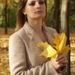 Woman in the park with yellow leaves — Stock Photo