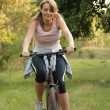 Woman cycling in a park — Stock Photo