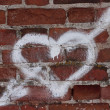 Heart pierced with an arrow on bricks - Stock Photo