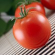 Tomatoes on a bamboo napkin - Stock Photo