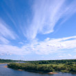 The dark blue sky with clouds over river - Stock Photo